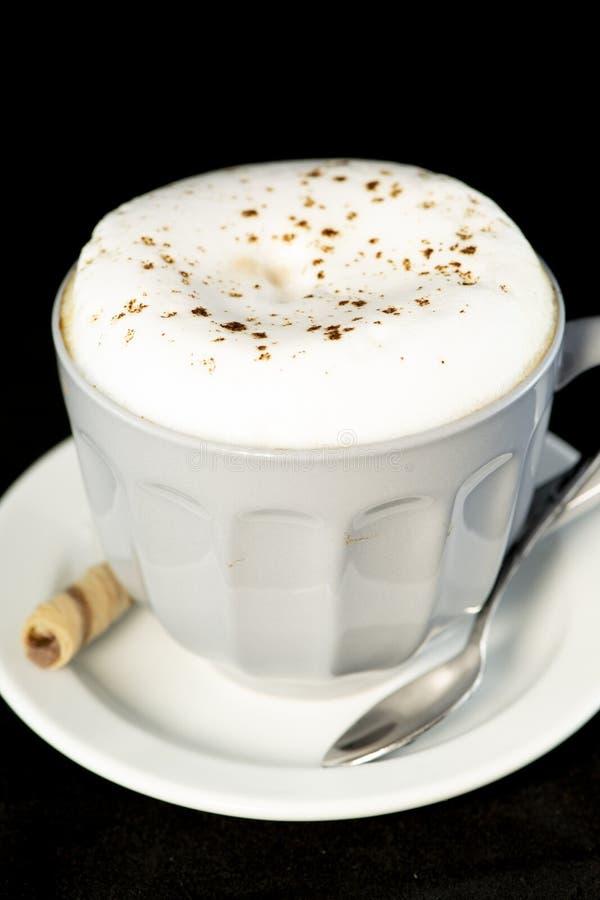 Le cappuccino délicieux a servi avec le petit pain de gaufrette de noisette de chocolat image libre de droits