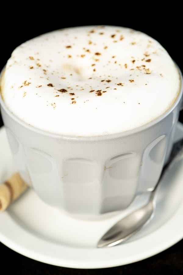 Le cappuccino délicieux a servi avec le petit pain de gaufrette de noisette de chocolat images stock