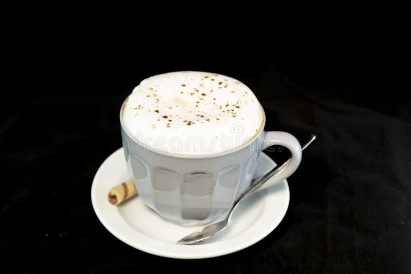 Le cappuccino délicieux a servi avec le petit pain de gaufrette de noisette de chocolat photo libre de droits