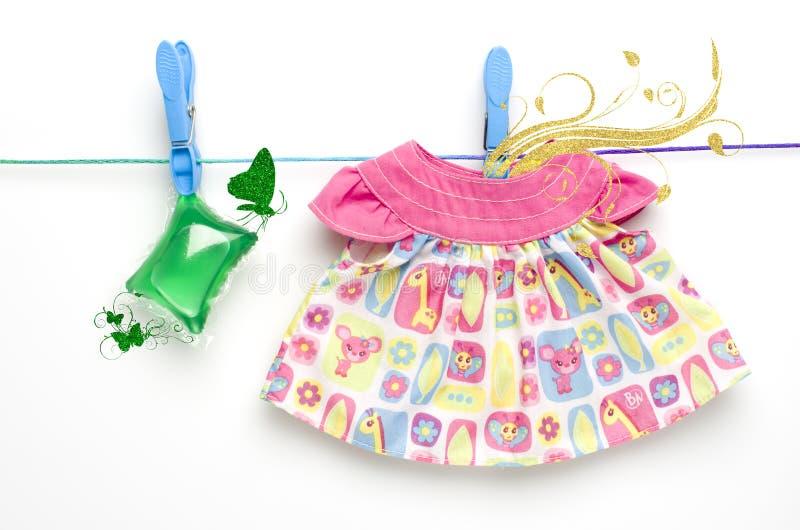 Le capsule di gel verdi ed il vestito della lavanderia che appendono sul lavaggio allineano su fondo bianco immagine stock libera da diritti