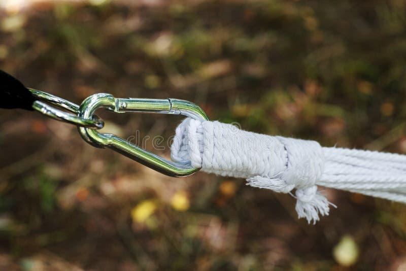 Le carabiner en métal avec la corde blanche épaisse, plan rapproché a tiré, foyer sélectif images libres de droits