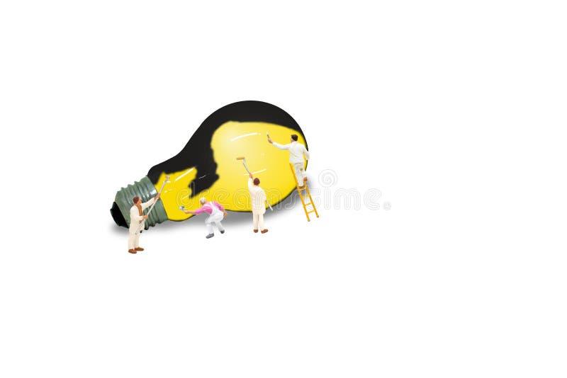 Le caractère miniature de figurine comme peintre peignent l'ampoule noire utilisant le pinceau et la couleur jaune illustration libre de droits