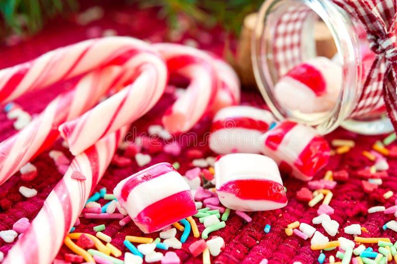 Le caramelle dolci rovesciate/hanno versato dal barattolo di vetro sul backgro di natale fotografie stock libere da diritti