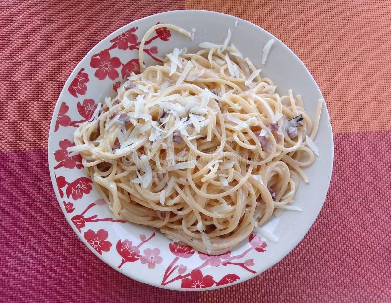 Le carbonara de spaghetti dans un plat avec des fleurs conçoivent photographie stock libre de droits