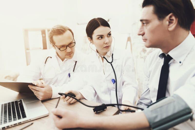 Le cardiologue expérimenté mesure la pression de l'homme adulte avec le tonometer Moniteur de preasure de sang de Digitals d'isol photographie stock