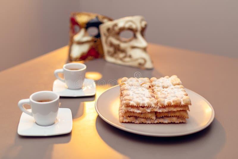 Le carnaval italien typique gaspille Chiacchiere di Carnevale épousseté avec en poudre Composition avec deux tasses de café et da photographie stock
