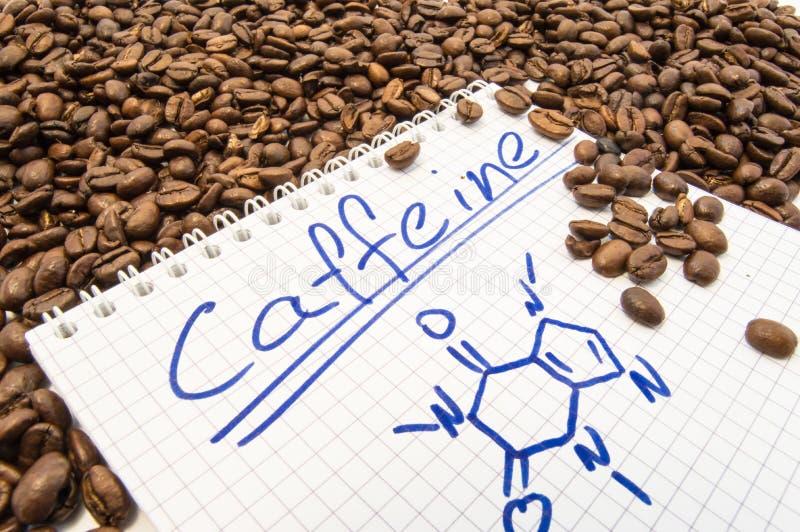 Le carnet avec de la caféine de titre des textes et la formule chimique peinte de la caféine est entouré par les grains prêts à e photographie stock libre de droits