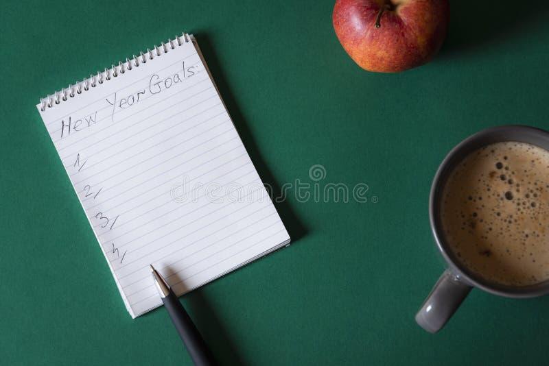 Le carnet avec des buts de nouvelle année énumèrent sur un bureau Au-dessus de la vue photo libre de droits