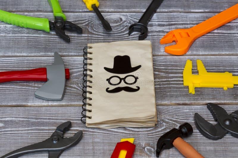 Le carnet d'un jour de pères heureux de félicitations est entouré par un outil de jouet sur un fond rustique photos stock