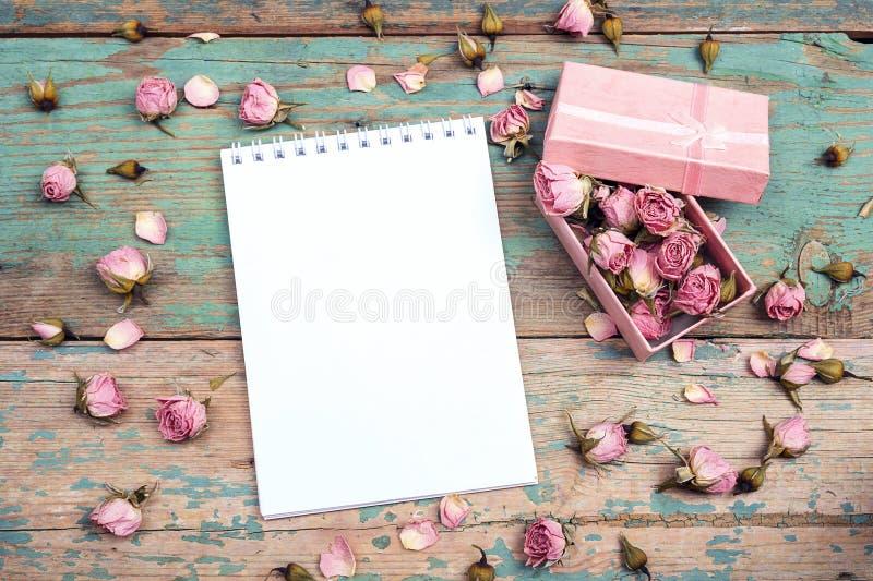 Le carnet et le boîte-cadeau ouverts propres avec le rose ont séché les fleurs roses photographie stock libre de droits