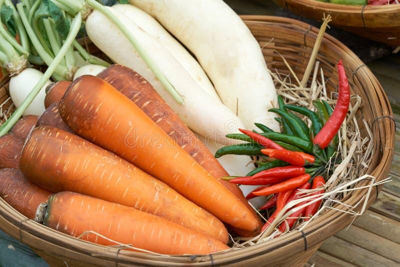 Le carote, i ravanelli ed i peperoni sono disposti sui canestri di legno Per essere usato come materia prima per la cottura del v immagine stock libera da diritti
