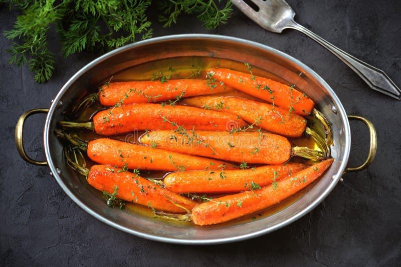 Le carote organiche con timo lustrato in arancio-miele sauce fotografia stock