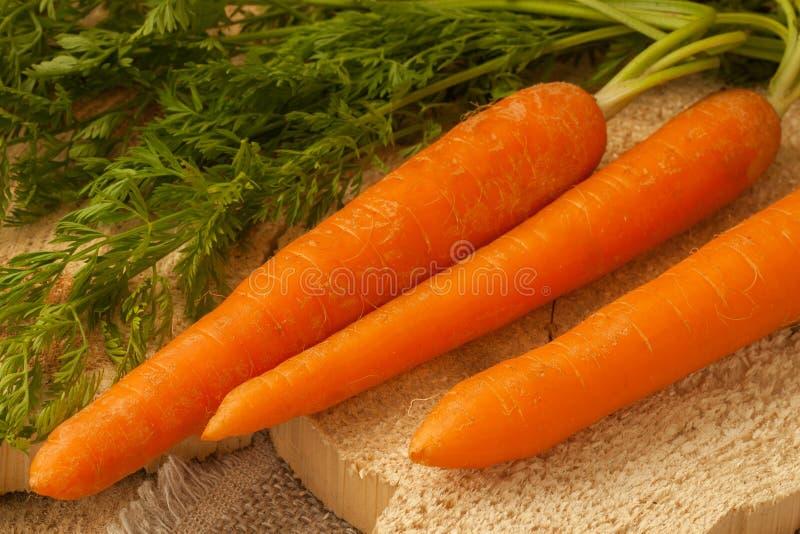 Le carote organiche su una superficie di legno, l'alimento dell'azienda agricola, GMO liberano fotografia stock libera da diritti