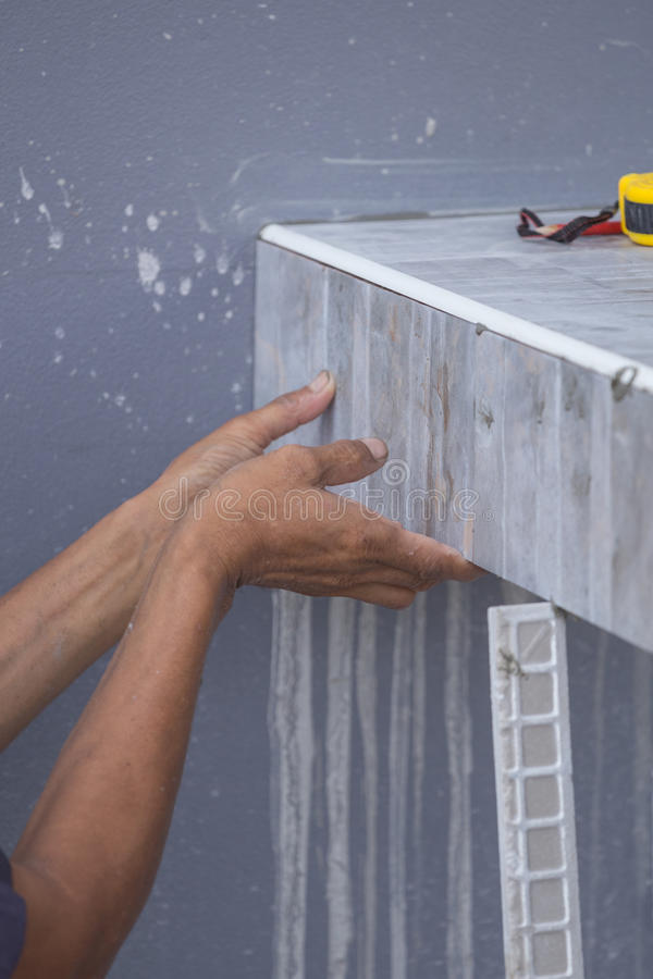 Le carreleur installent les carreaux de céramique image libre de droits