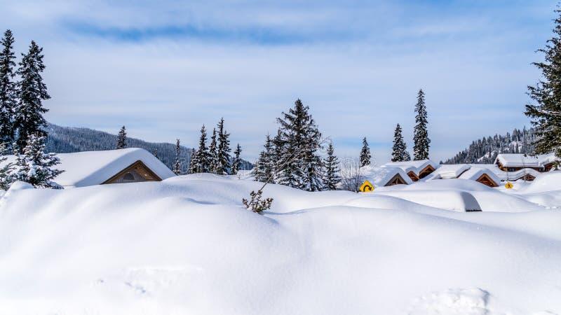 Le case della copertura del manto nevoso e le strade profonde del villaggio alpino del Sun alza fotografie stock libere da diritti