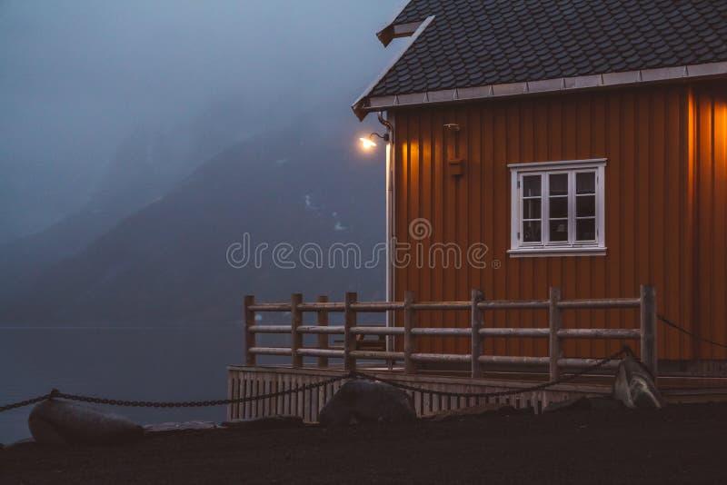Le case di rorbu della Norvegia e le rocce delle montagne sopra il fiordo abbelliscono le isole scandinave di Lofoten di vista di fotografia stock