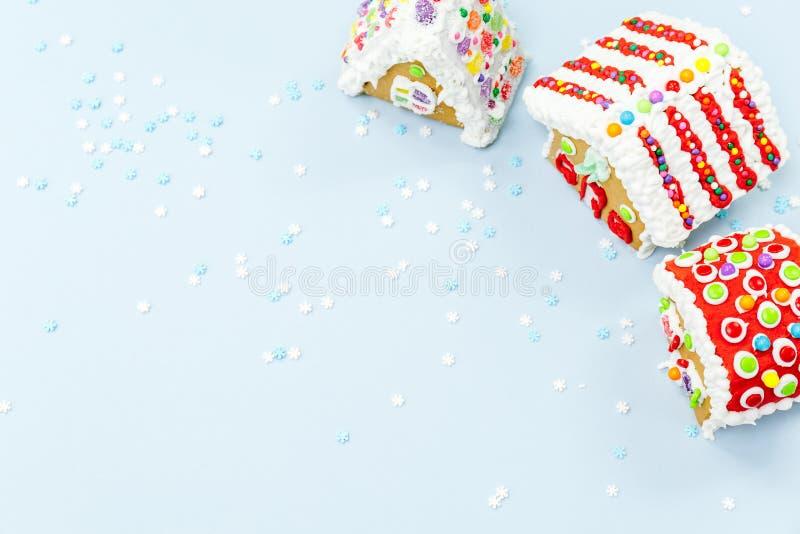 Le case e la neve di pan di zenzero spruzza sui precedenti blu CH fotografia stock libera da diritti