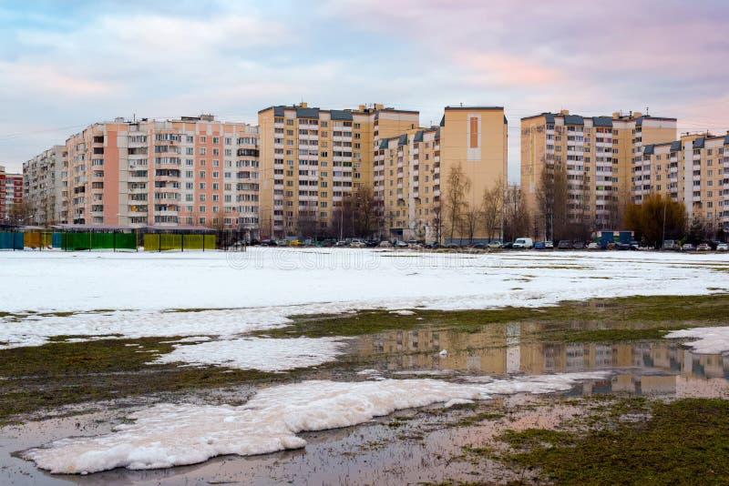 Le case ed il cielo urbani con le nuvole hanno riflesso in pozza da neve di fusione sulla via nel giorno di molla soleggiato fotografia stock libera da diritti