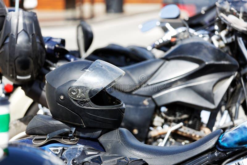 Le casque de moto se repose sur le siège d'une moto image stock