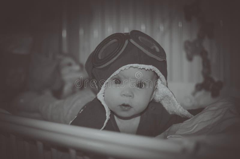 Le casque de nourrisson de bébé en vol est dans le lit photographie stock