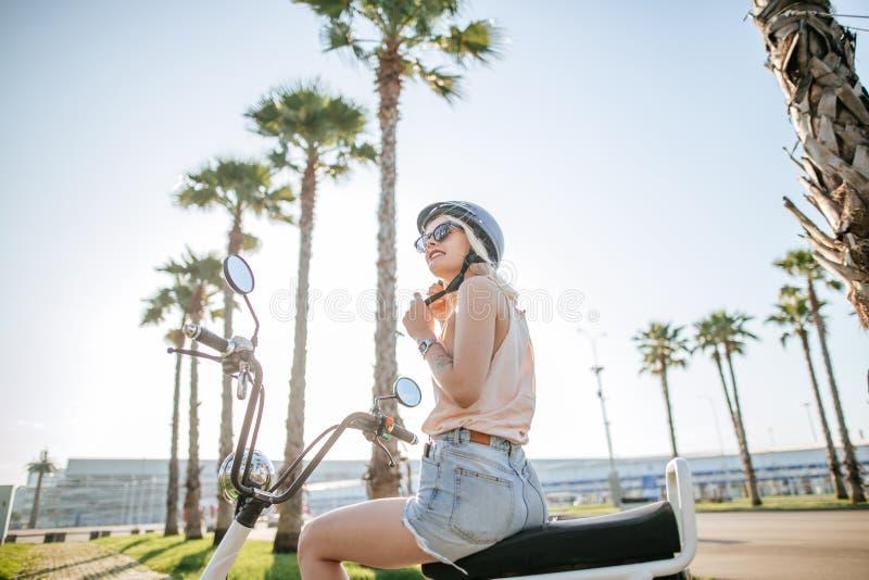 Le casque de port de jeune fille et les verres protecteurs se repose près de la bicyclette électrique photo libre de droits