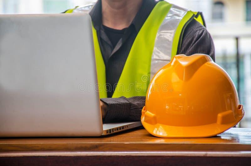 Le casque de sécurité et l'homme jaunes d'affaires dans l'industrie du bâtiment travaille dedans sur l'ordinateur images libres de droits