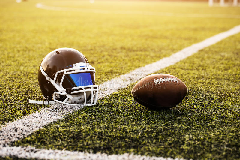 Le casque et la boule de football américain sur le modèle d'herbe verte pour le football folâtrent, terrain de football, terrain  photos libres de droits