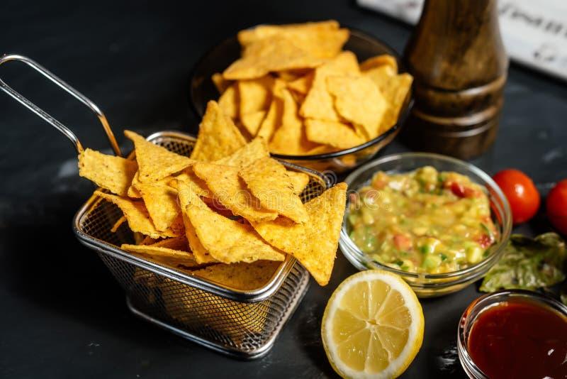 le casse-croûte avec des puces de maïs de tortilla, le Salsa épicé et le guacamole chaud délicieux sauce photographie stock