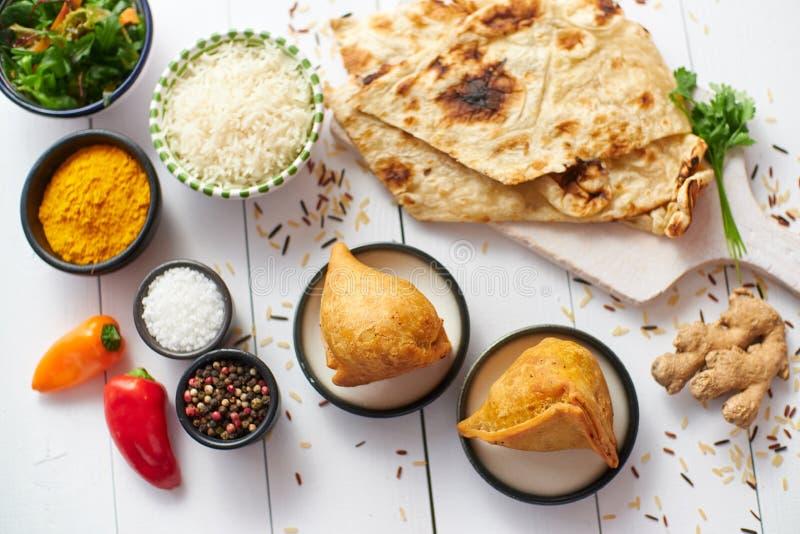 Le casse-cro?te indien traditionnel Samosa de nourriture a servi dans un plat sur une table en bois blanche image libre de droits