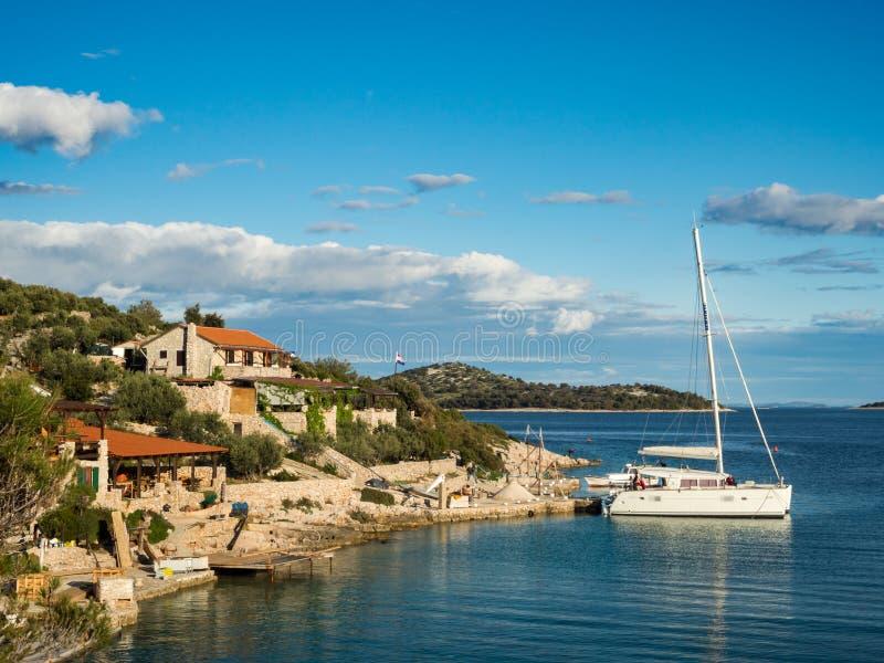 Le catamaran s'est accouplé dans une baie avec le restaurant en Croatie au coucher du soleil, île de Kaprije photo libre de droits