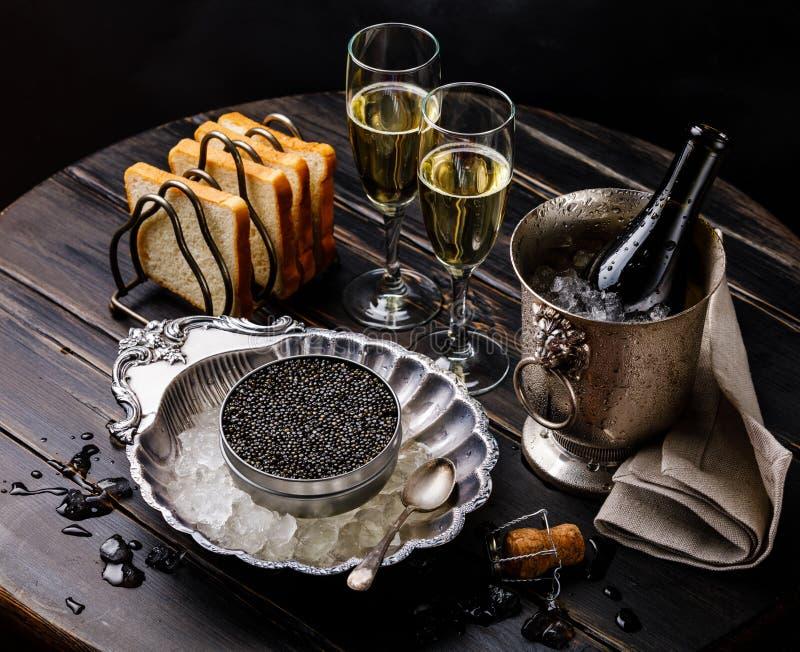 Le caviar noir peut dedans sur la glace en cuvette, pain et champagne argentés photographie stock libre de droits