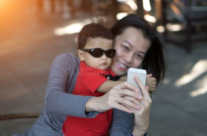 Le centre de la main asiatique de mère et le fils prenant le selfie photographient image stock