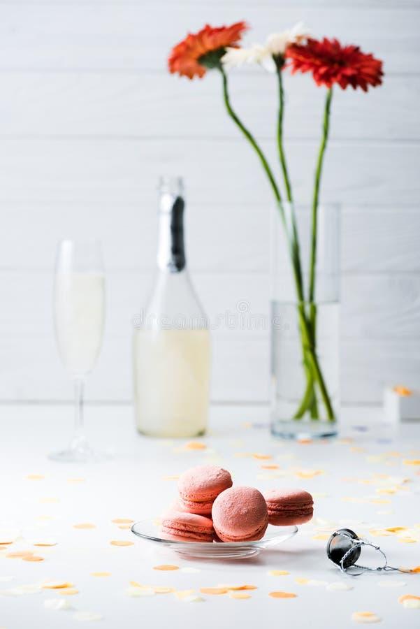 le centre sélectif des macarons, de la bouteille et du verre doux de champagne, bouquet de gerbera fleurit image stock