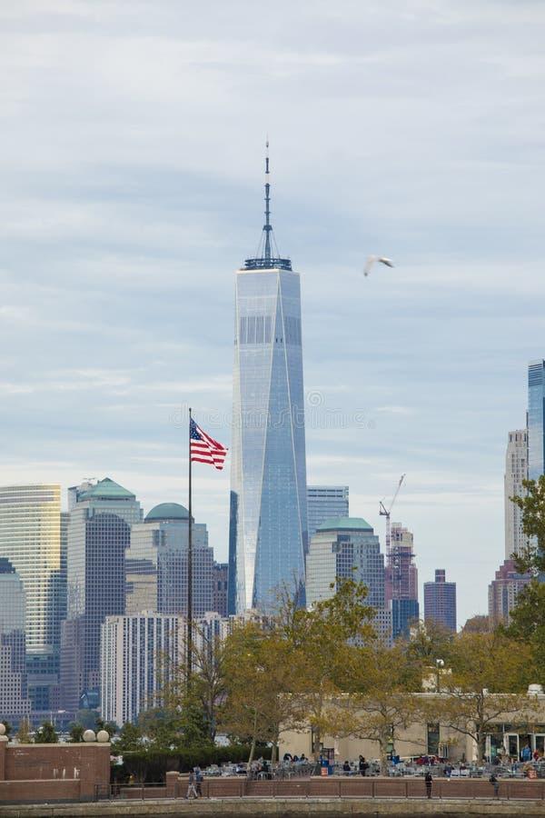 Le centre-ville de Manhattan et la tour de la Liberté vue depuis Ellis Island avec un drapeau au premier plan images stock