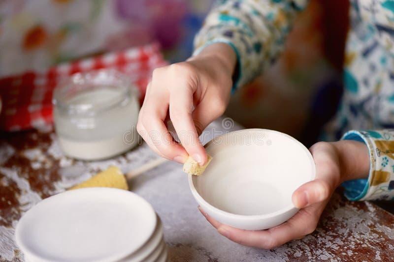 Le ceramist principal frotte un plat d'argile cuit au four Un atelier créatif photographie stock