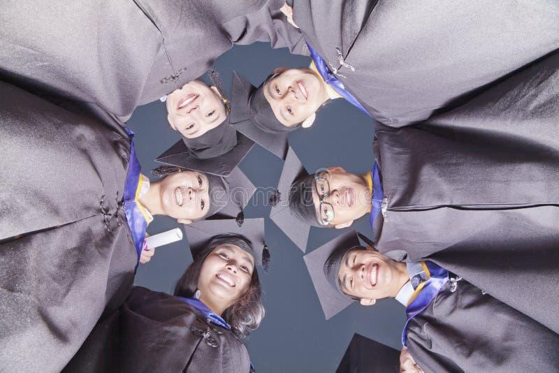 Le cercle des étudiants de troisième cycle de sourire dans l'obtention du diplôme habille le regard vers le bas, vue de dessous photographie stock