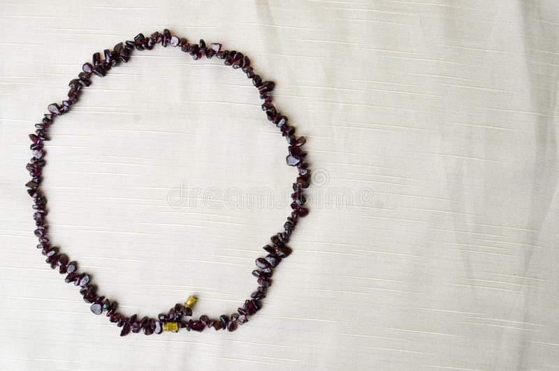 Le cercle est fait de belles perles femelles, colliers des pierres foncées brunes, ambres avec un fond de tissu beige photo libre de droits
