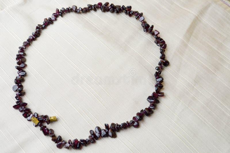 Le cercle est fait de belles perles femelles, colliers des pierres foncées brunes, ambres avec un fond de tissu beige photo stock