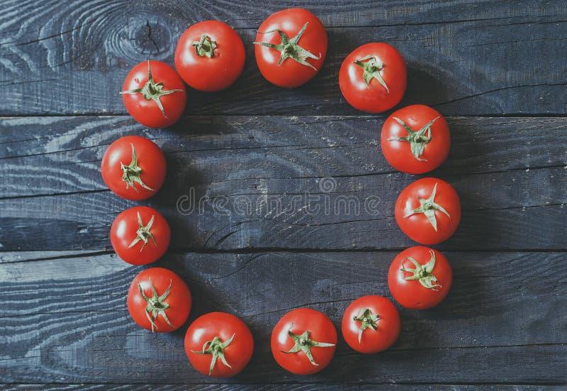 Le cercle a formé avec les tomates fraîchement sélectionnées sur le fond en bois rustique foncé photo stock
