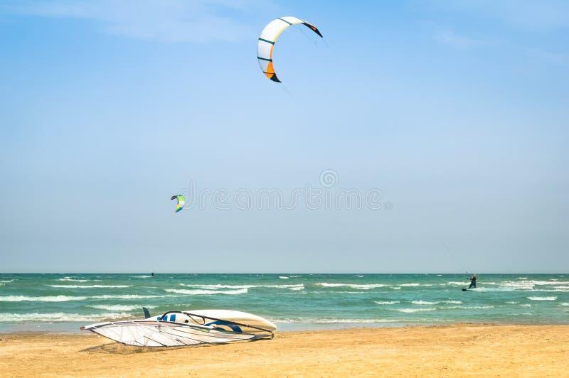 Le cerf-volant surfant en plage venteuse avec font de la planche à voile conseil photographie stock libre de droits