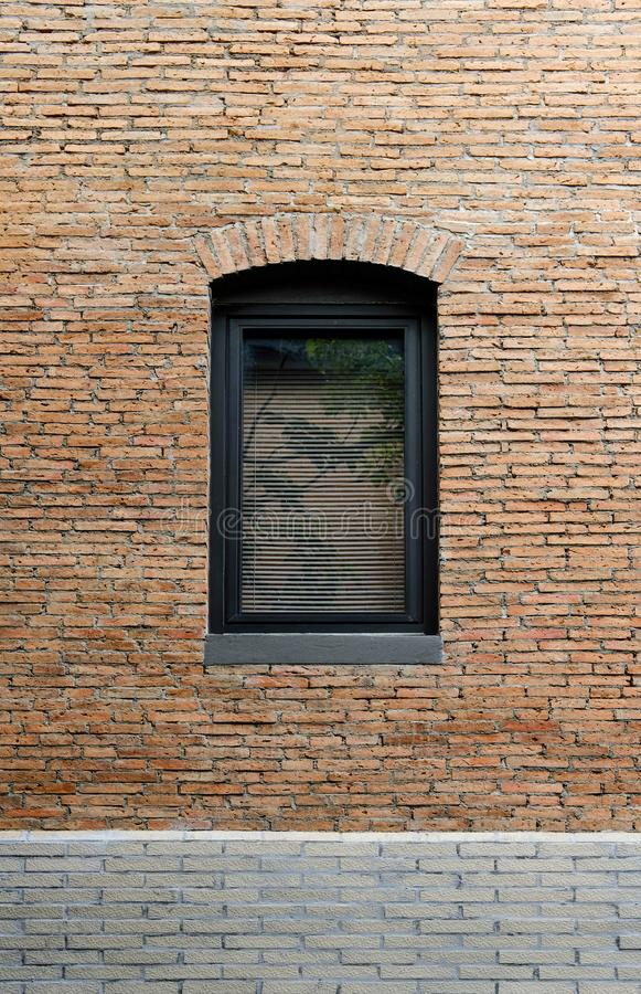 Le châssis de fenêtre en aluminium noir dans le mur de construction a fait de la brique rouge images libres de droits