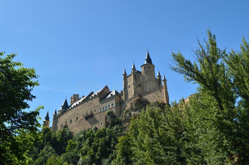 Le château d'Alcazar vu de la rivière qui fonctionne par la vallée qui règne à Ségovie a légèrement attrapé par un petit verger a image stock