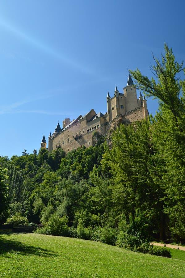 Le château d'Alcazar vu de la rivière qui fonctionne par la vallée qui règne à Ségovie a légèrement attrapé par un petit verger a photo libre de droits