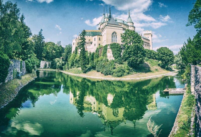 Le château de Bojnice est reflété dans l'eau, filtre analogue images stock