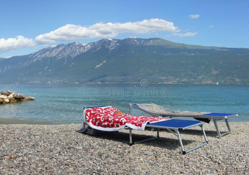 Le chaise-lounge di Sun nel lago di polizia puntellano, l'Italia fotografia stock libera da diritti