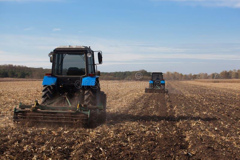 Le champ d'inclinaison La grande charrue bleue du traktor deux a labouré la terre après moisson de la culture de maïs photographie stock libre de droits