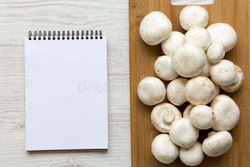 Le champignon de paris répand sur le conseil en bambou avec le bloc-notes au-dessus du fond en bois blanc, vue supérieure photographie stock libre de droits