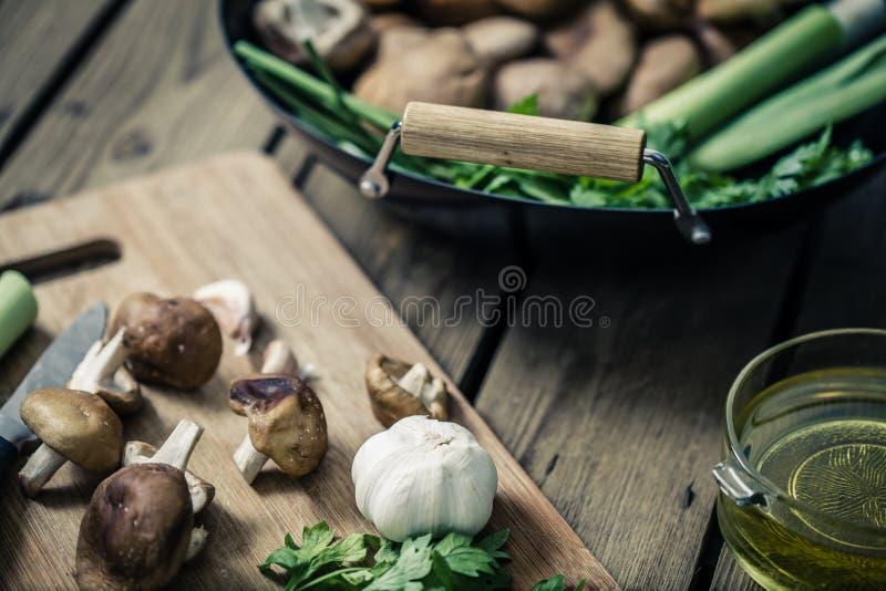 Le champignon de Shitake se préparent à la cuisson sur le wok et la plaque de découpage photographie stock