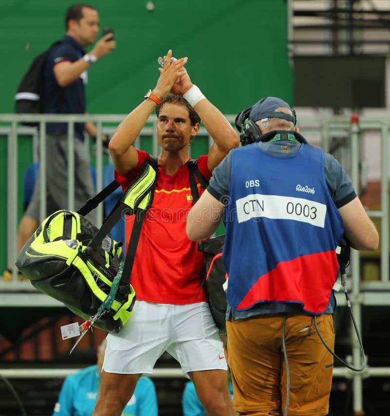 Le champion olympique Rafael Nadal de l'Espagne célèbre la victoire après que le ` s d'hommes choisisse le premier match de rond  image libre de droits