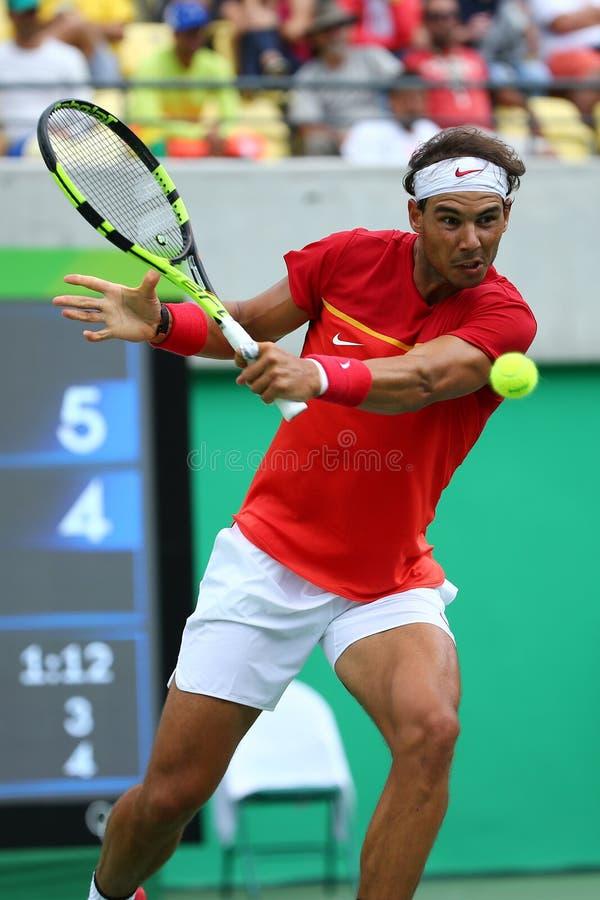 Le champion olympique Rafael Nadal de l'Espagne dans l'action pendant le ` s des hommes choisit autour de quatre de Rio 2016 Jeux photographie stock libre de droits